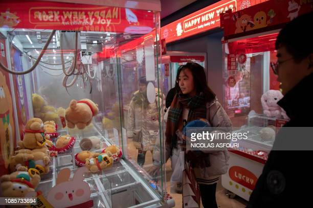 A young woman fails to grab a teddy bear in a game shop in Beijing on January 21 2019 China's economy grew at its slowest pace in almost three...