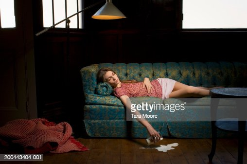 Young Woman Falling Asleep On Sofa Spilling Milk From