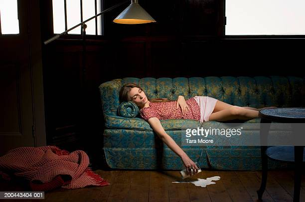 Young woman falling asleep on sofa spilling milk from glass on floor