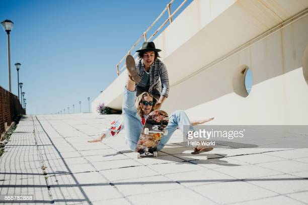 Young woman falling off skateboard