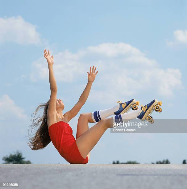 Young woman falling with roller skates