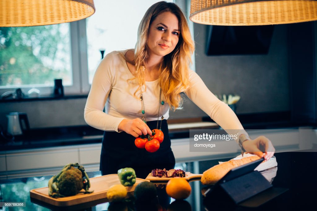 Young woman fallowing the recipe from a digital tablet and cooking in the kitchen : Stock Photo