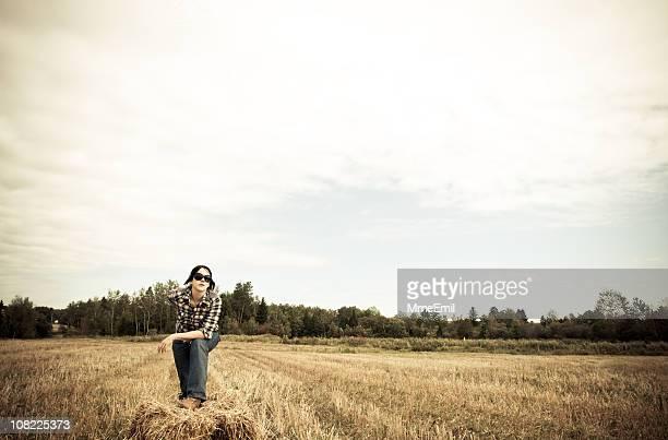 Jovem agricultor Ajoelhar de Hay Bale em Campo