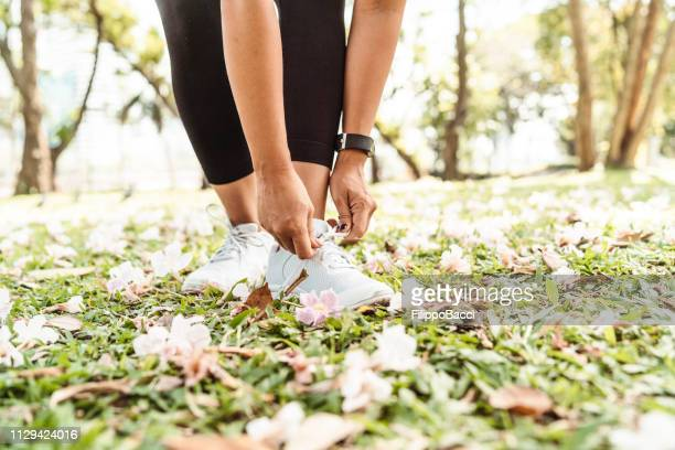 young woman fastening her shoes at the park - lace fastener stock pictures, royalty-free photos & images