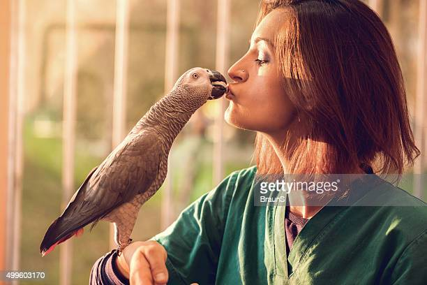 young woman feeding a parrot from her mouth. - parrot stock pictures, royalty-free photos & images