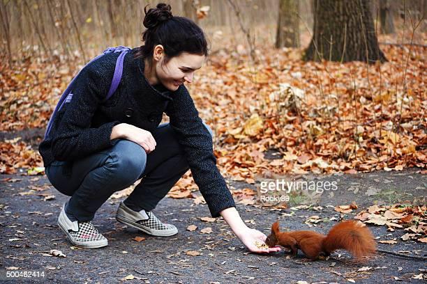 Young woman feeding a squirrel