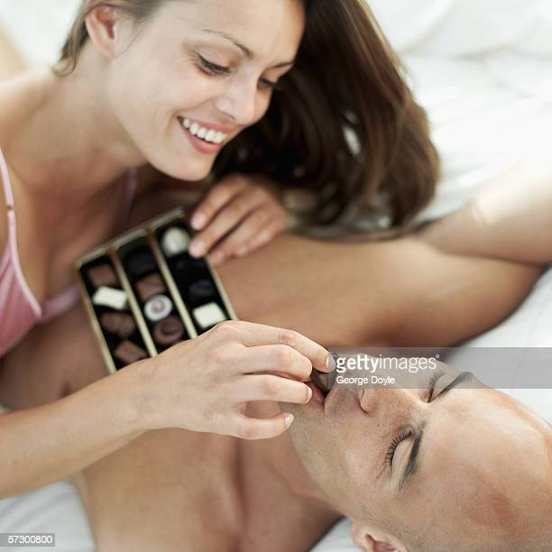 young woman feeding a young man chocolates in bed - couple chocolate stock pictures, royalty-free photos & images