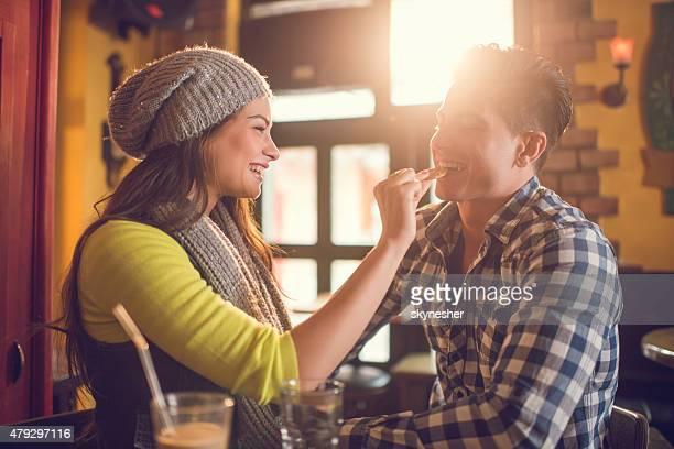 Mujer joven alimentar a su novio con una cookie en el café.