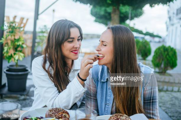 young woman feeding her friend in a street restaurant - nutrire foto e immagini stock