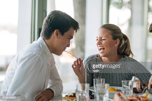 Young Woman Feeding Her Man In Restaurant.