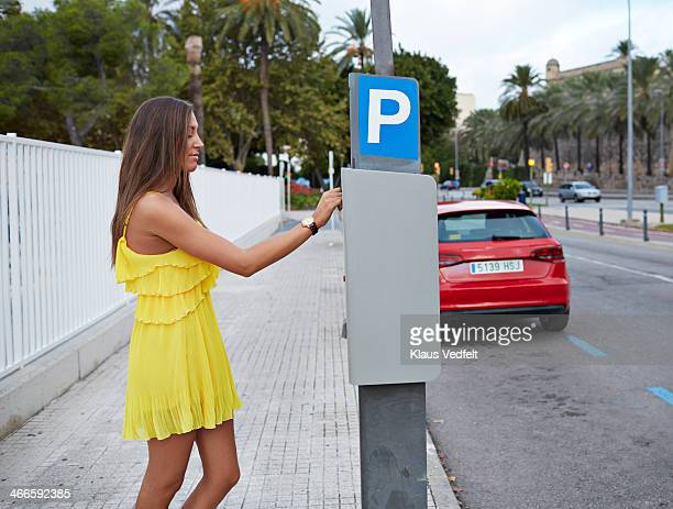 Young woman feeding parking meter