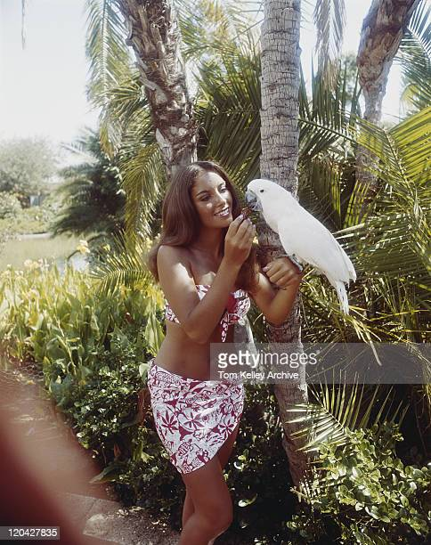 Young woman feeding parrot, smiling