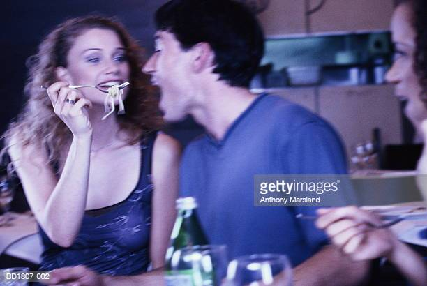 Young woman feeding pasta to young man with fork (blurred motion)
