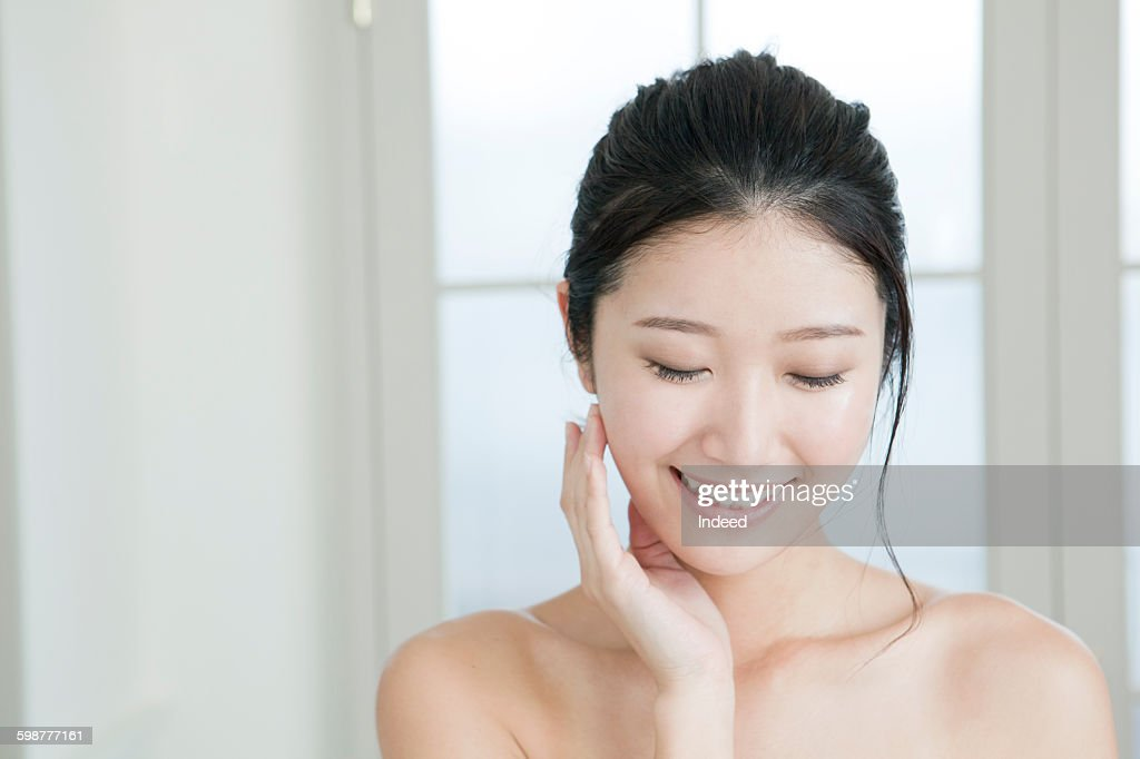 Young woman feeling facial skin : Stock-Foto