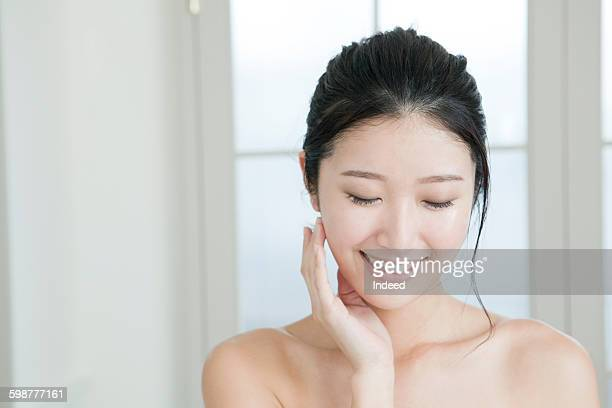 Young woman feeling facial skin