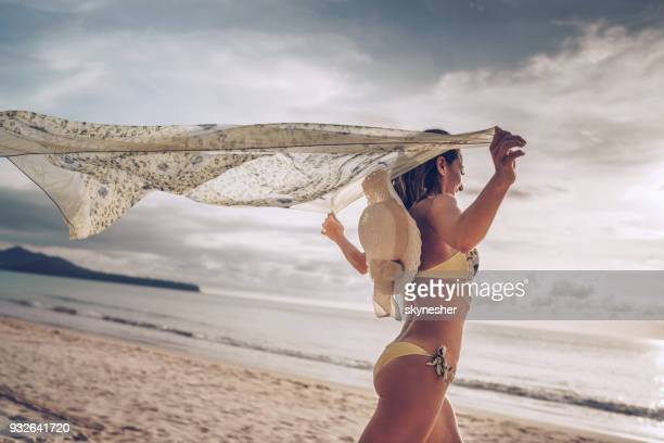 young woman feeling free while running with a shawl on the beach. - shawl stock pictures, royalty-free photos & images