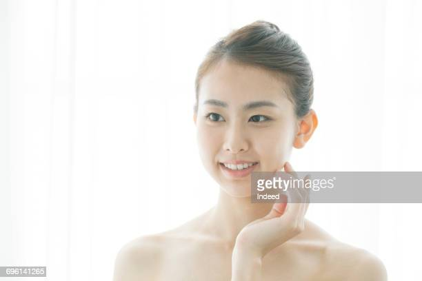 Young woman feeling her face skin