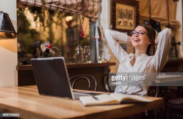 Junge Frau Gefühl erleichtert, nachdem spät in die Nacht gearbeitet wird.