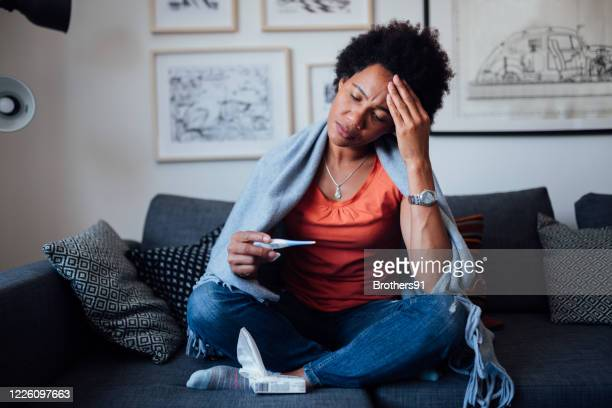 young woman feeling symptoms of an illness - fever stock pictures, royalty-free photos & images