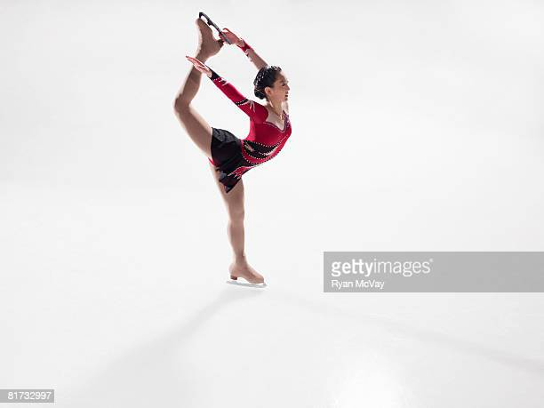 Young woman figure skater performing a Bielman. (alternative spelling is 'Biellmann')