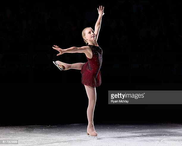 Young woman figure skater skating one one foot with arms raised.