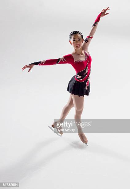 Young woman figure skater standing in finishing pose.