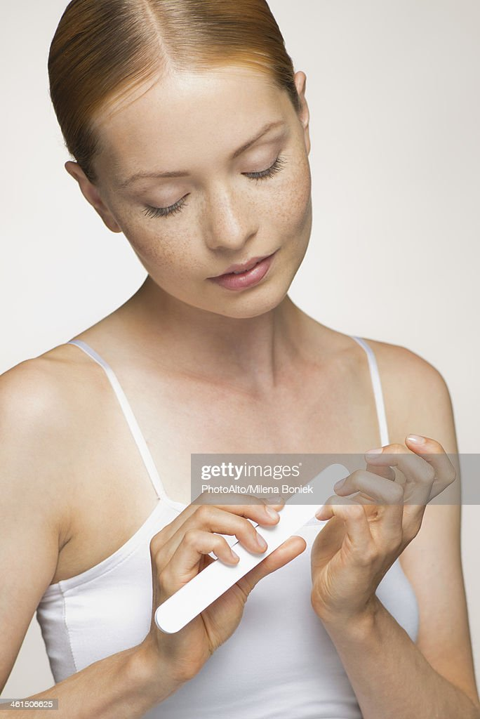 Young woman filing fingernails : Stock Photo
