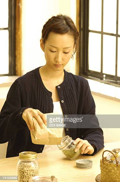 Young woman filling a jar with beans