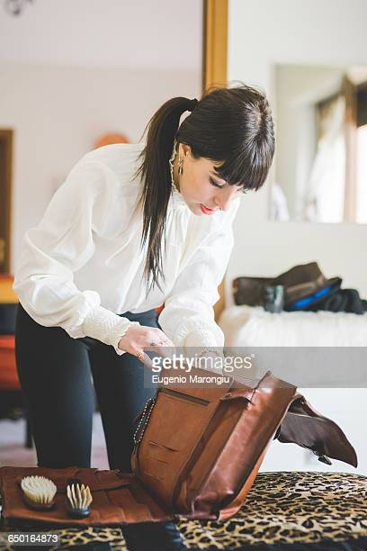 young woman filling bag in bedroom - borsetta da sera foto e immagini stock