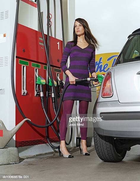 Young woman filling fuel in car at petrol station
