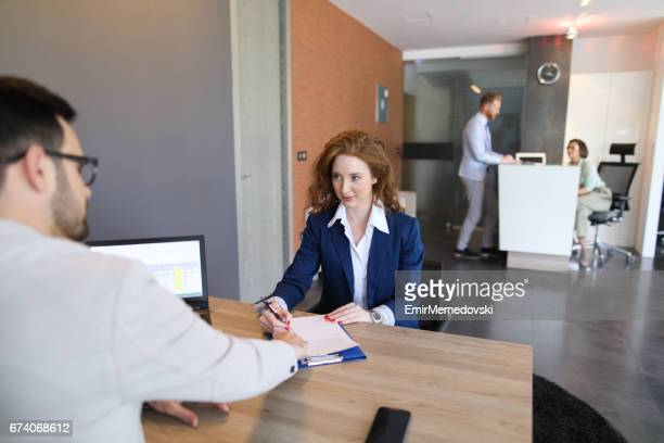 Young woman filling out application form at job interview.
