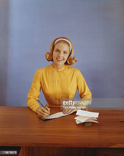 Young woman filling out bank slip, smiling, portrait