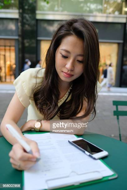 young woman filling out paper on street - survey stock photos and pictures