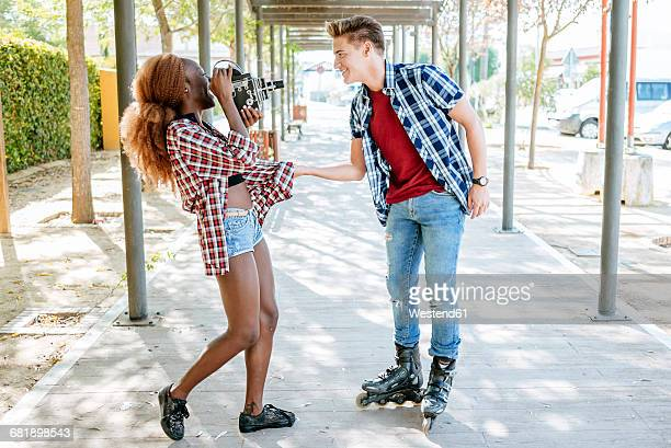 Young woman filming her boyfriend on inline skates with an old-fashioned camera