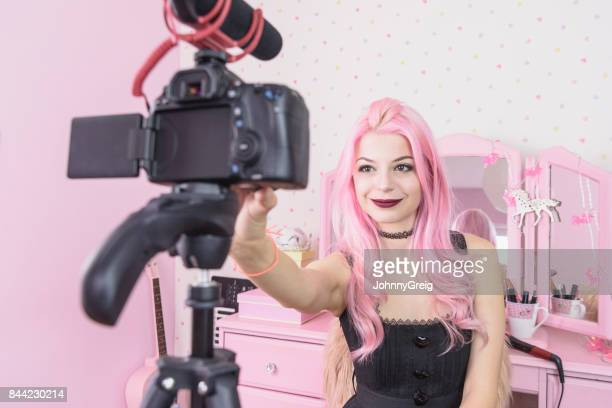 Young woman filming video blog on camera in bedroom