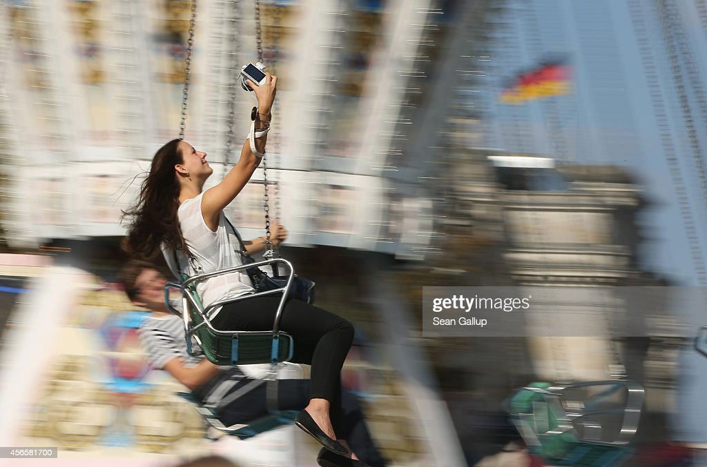 A young woman films herself as she sits on a swing ride near the Reichstag on German Unity Day (Tag der Deutschen Einheit) on October 3, 2014 in Berlin, Germany. Germany is celebrating the 24th anniversary of the day when former West Germany and East Germany reunited into modern Germany in 1990 following the end of the Cold War. This year Germany will also celebrate the 25th anniversary of the fall of the Berlin Wall that heralded the collapse of communist authority in East Germany.