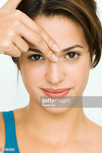 Young woman fingers on forehead, portrait