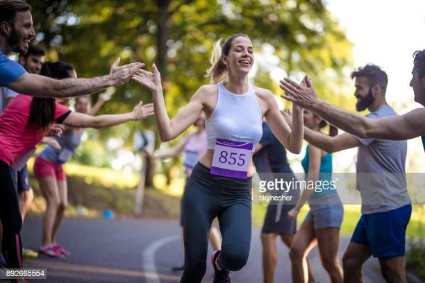 young woman finishing marathon race and greeting with group of supporters. - finish line stock pictures, royalty-free photos & images