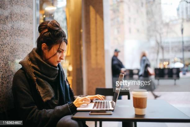 jonge vrouw afwerking werk in het san francisco café - na werktijd stockfoto's en -beelden
