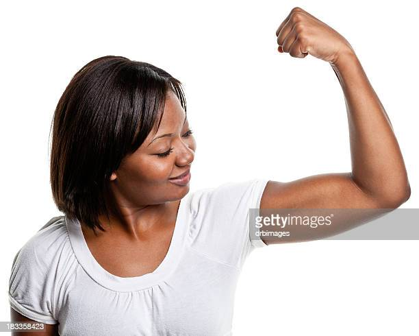 young woman flexes bicep muscle - flexing muscles stock pictures, royalty-free photos & images