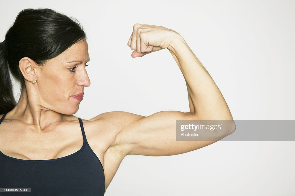 Young woman flexing muscles in studio, portrait : Stock Photo