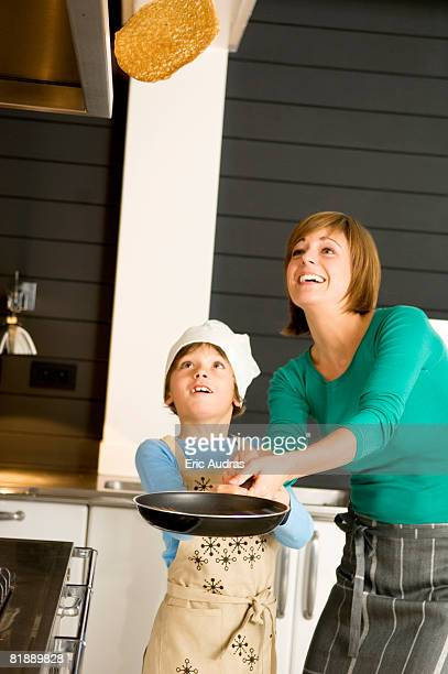 Young woman flipping a pancake with her son
