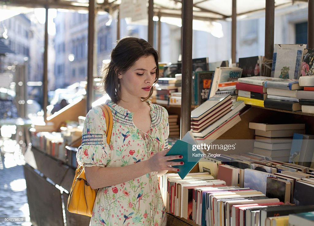 young woman flipping through book at bookstall : Stock Photo