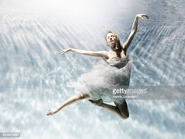 young woman floating gracefully under water