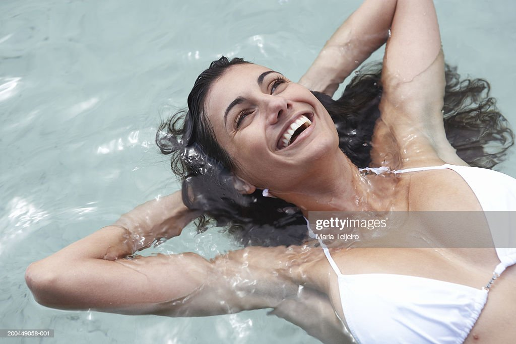 Young woman floating in sea, hands behind head, laughing, close-up : Stock Photo