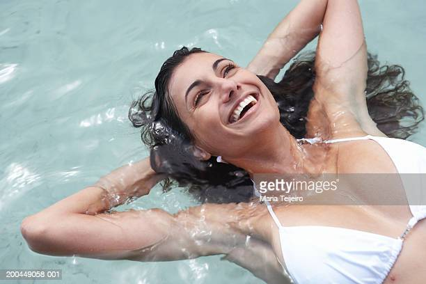 Young woman floating in sea, hands behind head, laughing, close-up