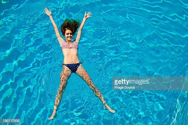 young woman floating in  swimming pool - girl with legs spread stock photos and pictures