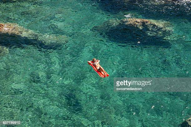 Young woman floating on pool mattress in the ocean