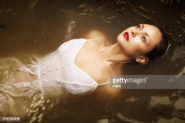 young woman floating on water in the swamp - dead female bodies stockfoto's en -beelden