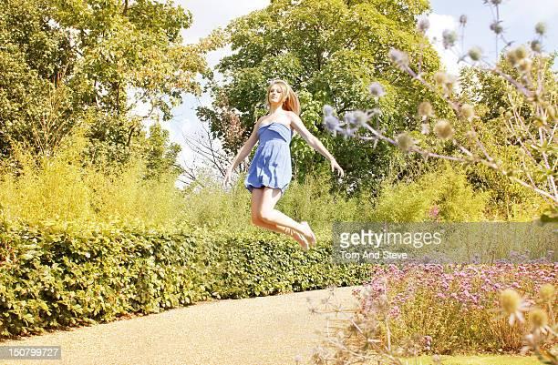 young woman floating through a wild summer garden - minijurk stockfoto's en -beelden